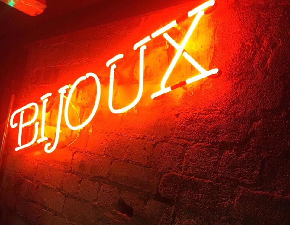 Bijoux Bar Review, featuring an image of the work Bijoux lit up in red against a brick wall
