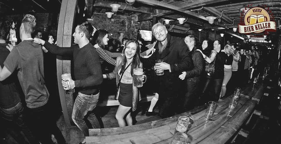 A black and white image of some people standing and dancing in Stein Bier Keller, one of Newcastle's best nightclubs