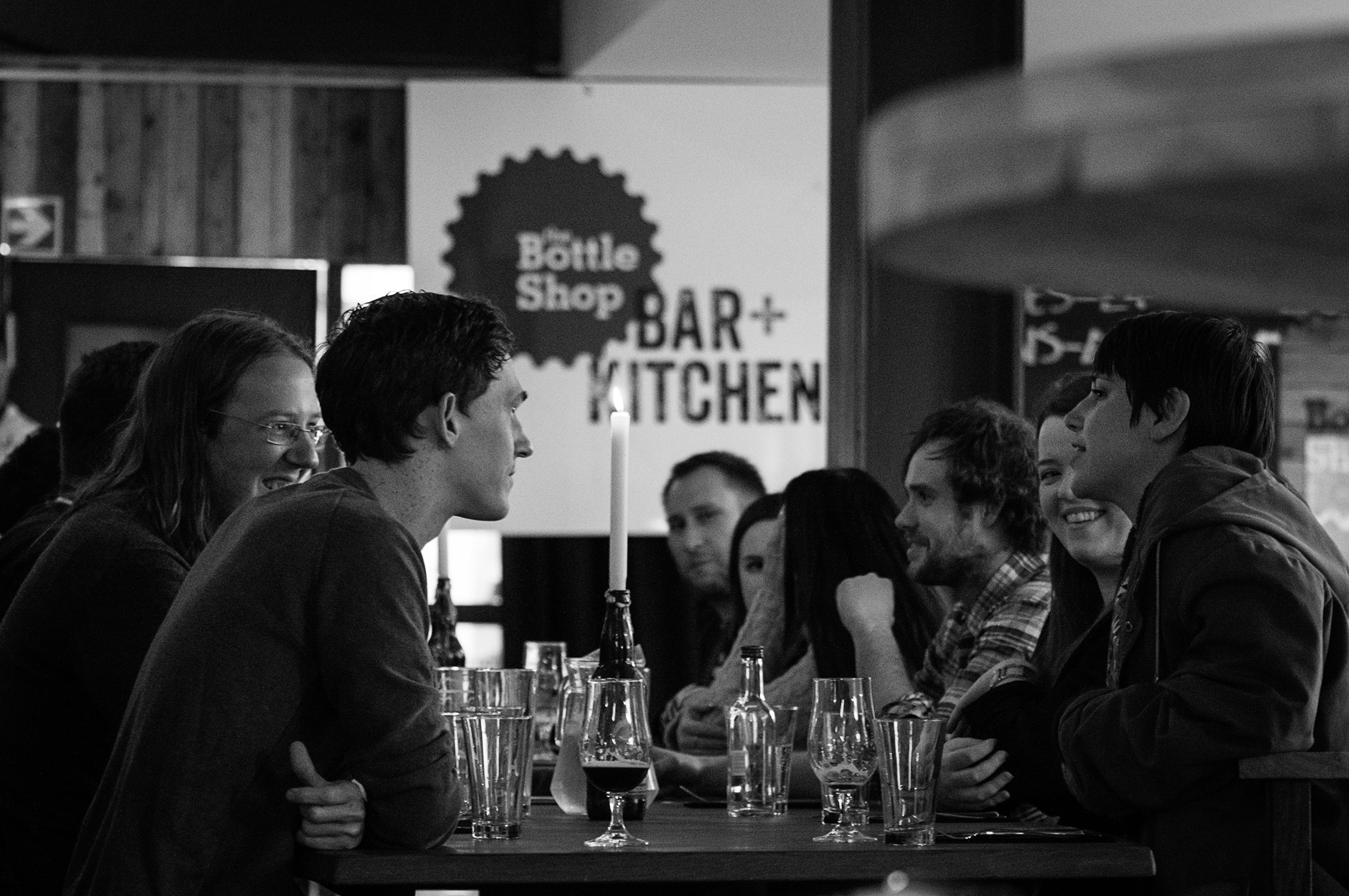Newcastle's Craft Beer Bars, featuring a black and white image of people sat at a table at The Bottle Shop Bar & Kitchen