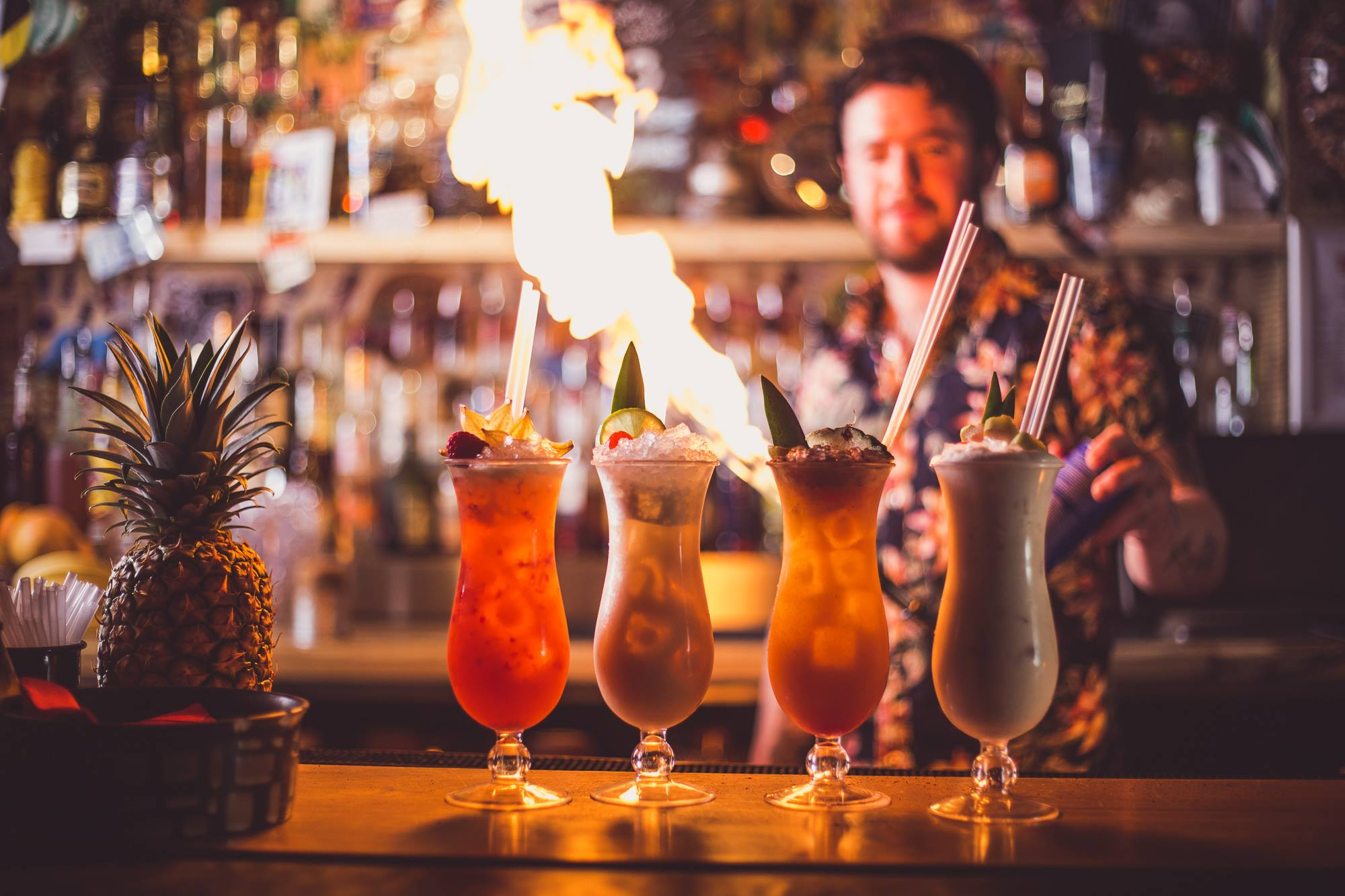 Party Universities, with an image of four cocktails on a table, with a bartender and flames in the background